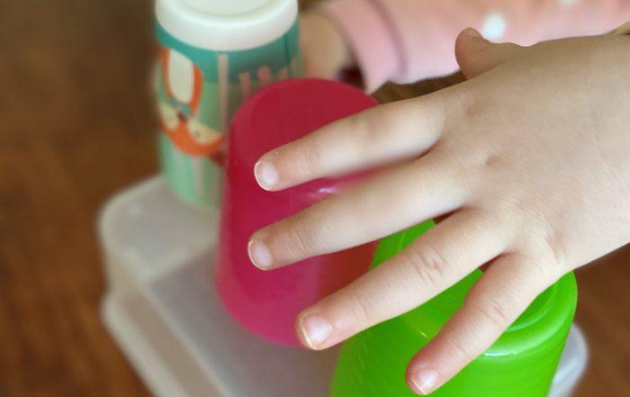 Kind spielt mit Bechern